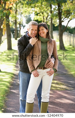 Portrait Of Romantic Couple Enjoying Outdoor Walk Through Autumn Park