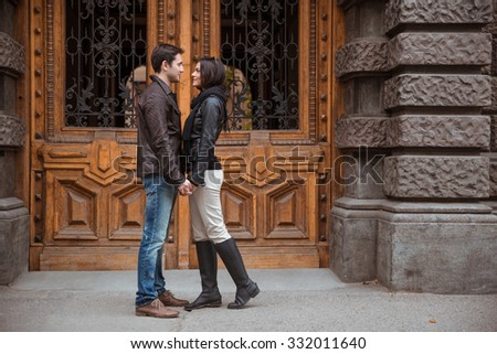 Portrait of romantic couple standing outdoors with old wooden door on bacground - stock photo