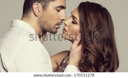 Portrait of romantic couple touching and kissing each other - stock photo