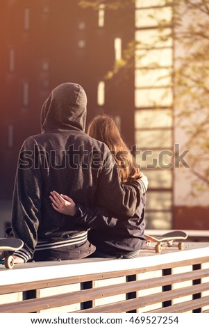 Portrait of romantic couple with skateboards hugging over city town background
