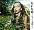 Portrait of romantic girl in flower meadow - stock photo