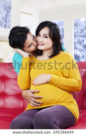 Portrait of romantic man kissing his pregnant wife on the sofa with winter background - stock photo