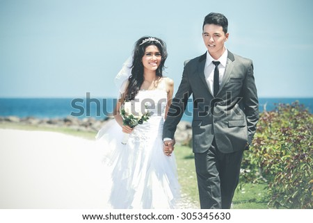 portrait of romantic newlywed couple holding hand and walking at seashore in sunny day - stock photo