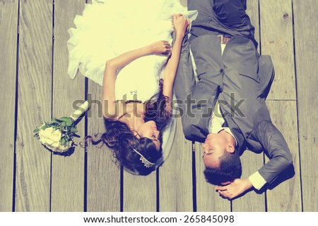 portrait of romantic newlywed couple lying down together in sunny day - stock photo