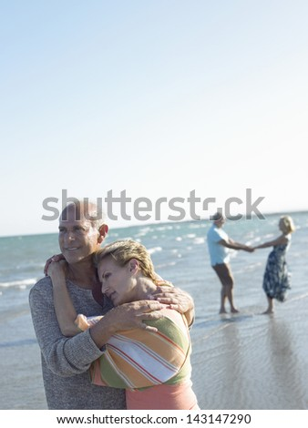 Portrait of romantic senior couple embracing with friends dancing in background on tropical beach - stock photo