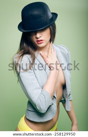 Portrait of romantic sexy beautiful young lady in bowler hat and yellow underwear with bare breasts and stomach on copy space background - stock photo