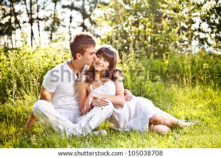 Portrait of romantic teenage couple sitting in park - stock photo