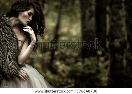 Portrait of romantic woman in beautiful dress in fairy forest