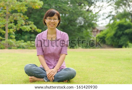 portrait of romantic, woman with short hair lying on green grass - stock photo