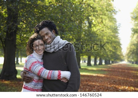 Portrait of romantic young couple embracing at park - stock photo