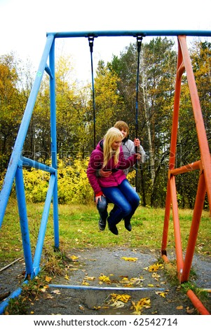Portrait Of Romantic Young Couple In Autumn Season On Playground Swinging