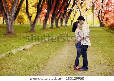 Portrait of romantic young couple kissing on the road in autumn day - stock photo