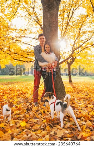 Portrait of romantic young couple outdoors in autumn park with dogs - stock photo