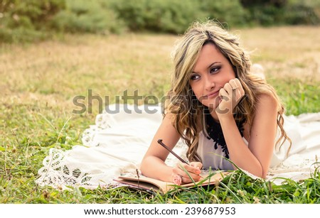 Portrait of romantic young woman writing in a diary lying down over the grass. Relax outdoor time concept.