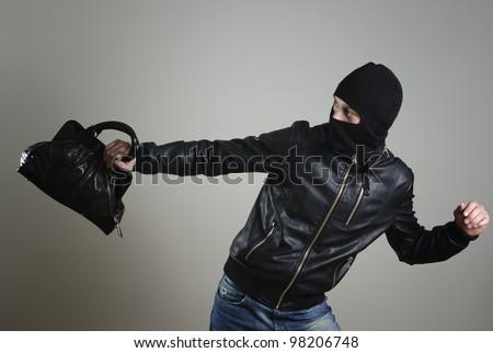 Portrait of running male burglar with a handbag. - stock photo