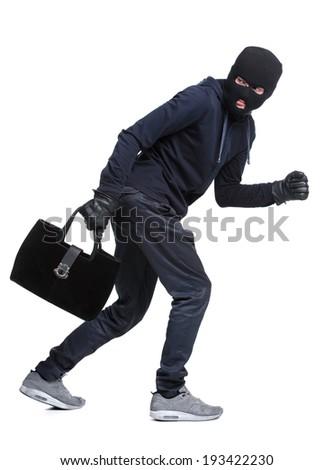 Portrait of running male burglar with a handbag. Isolated on white background - stock photo