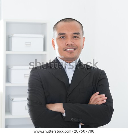 Portrait of 30s Asian Muslim business man smiling, real modern office background. - stock photo