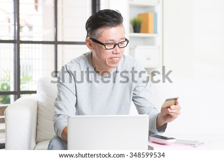 Portrait of 50s mature Asian man using computer doing online shopping with credit card, sitting on sofa at home, senior retiree indoors living lifestyle.