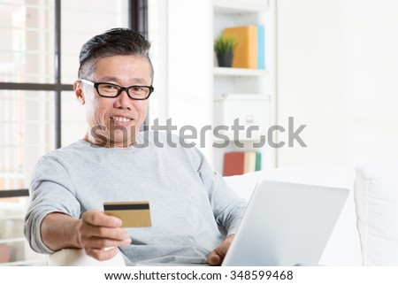 Portrait of 50s mature Asian man using computer paying bill with credit card, sitting on sofa at home, senior retiree indoors living lifestyle.