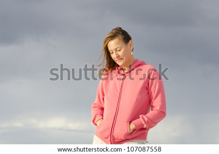 Portrait of sad and depressed looking mature woman in pink sweater, at beach, isolated with storm clouds as background and copy space. - stock photo
