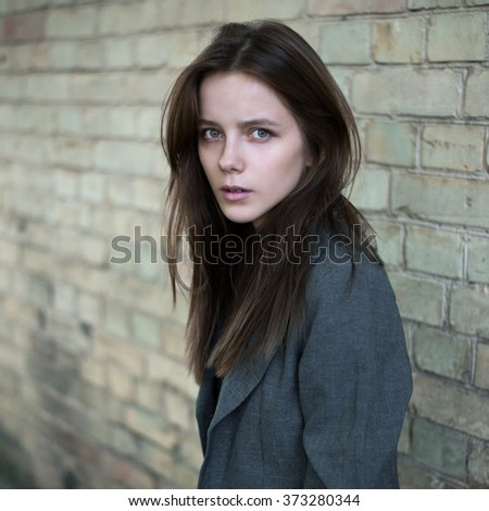 Portrait of sad beautiful young girl on a background of a brick wall