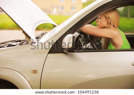 Portrait of sad beautiful young woman in car. - stock photo