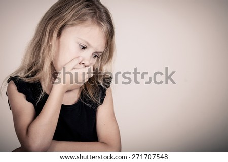 Portrait of sad blond little girl sitting near white wall - stock photo