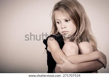 Portrait of sad blond little girl sitting near white wall - stock photo