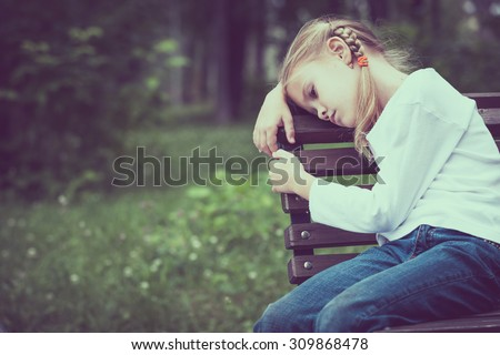 Portrait of sad blond little girl sitting on bench at the day time. - stock photo