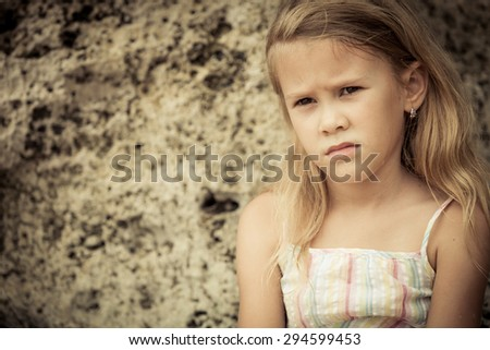 Portrait of sad blond little girl sitting on the beach at the day time