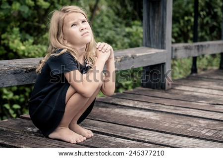 Portrait of sad blond little girl sitting on the bridge at the day time - stock photo