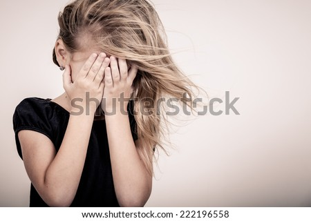 Portrait of sad blond little girl standing near wall - stock photo