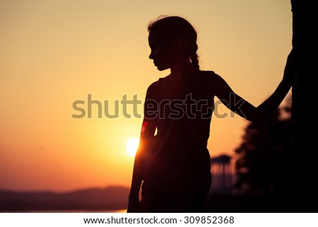 Portrait of sad blond little girl standing on the beach at sunset time. - stock photo