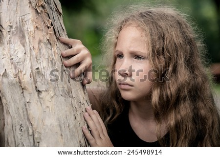 Portrait of sad blond teen girl  at the day time - stock photo