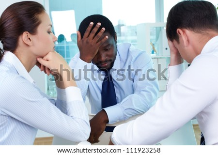 Portrait of sad business team sitting in office - stock photo