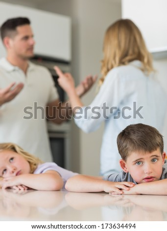 Portrait of sad children leaning on table while parents arguing in background at kitchen - stock photo