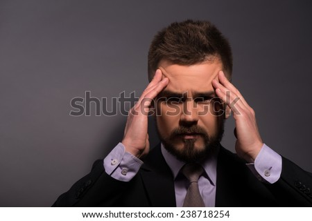 Portrait of sad disappointed  handsome stylish man in elegant black suit and beige tie  touching his forehead closing eyes  with copy place  - stock photo