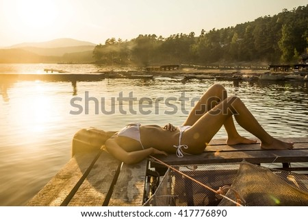 portrait of sad dreaming beautiful girl lying on wooden and metal pontoon. Cute woman thinking about something above water reflection texture against summer sunset background - stock photo
