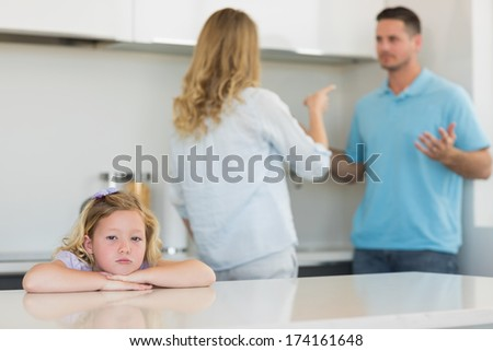 Portrait of sad girl leaning on table while parents arguing in background at home - stock photo
