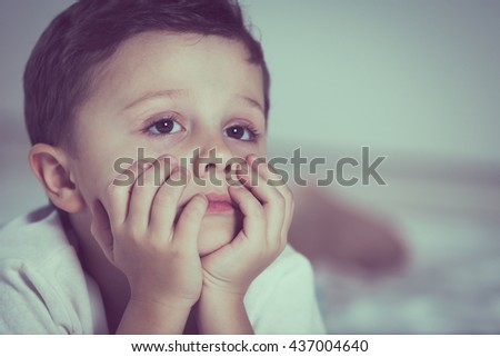 Portrait of sad little boy lying on bed at the day time. Concept of sad childhood. - stock photo