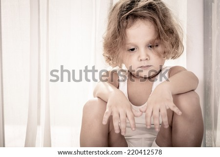 Portrait of sad little boy sitting near the window - stock photo