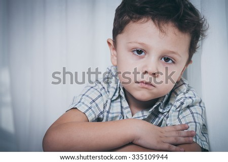 Portrait of sad little boy sitting near the window at home at the day time - stock photo
