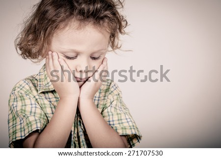 Portrait of sad little boy standing near white wall - stock photo