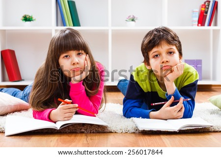 Portrait of sad little girl and little boy,they must  stay at home and do their homework,but they would rather play outside.We would rather play - stock photo