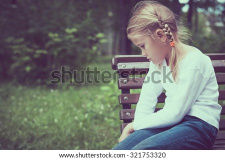 Portrait of sad little girl at the day time. - stock photo