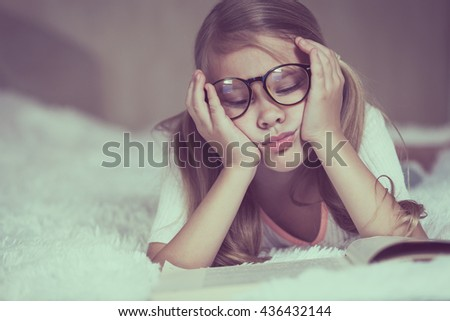 Portrait of sad little girl lying on bed at the day time. Concept of sad childhood. - stock photo