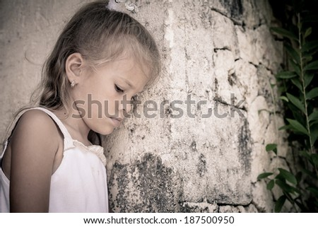 Portrait of sad little girl standing near stone wall in the day time