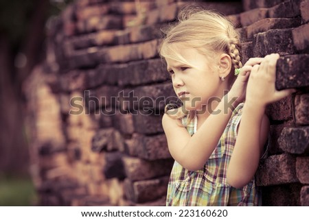 Portrait of sad little girl standing near the wall at the day time - stock photo