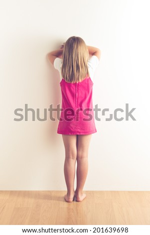 portrait of sad little girl standing near wall. studio shot - stock photo