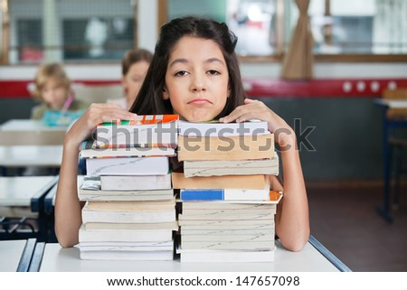 Portrait of sad little schoolgirl resting chin on stacked books at desk in classroom